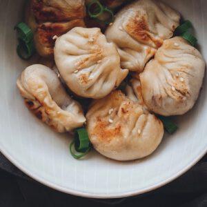 Vegane Dumplings in einer Schüssel mit Frühlingszwiebeln