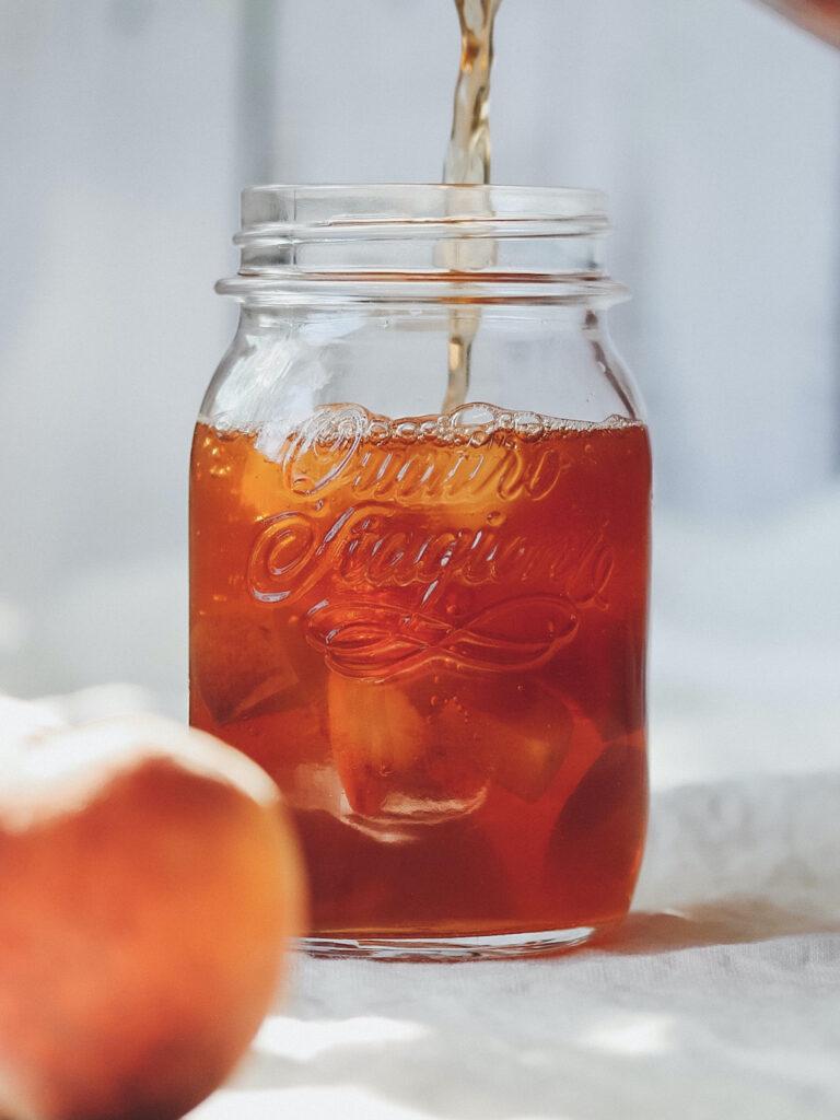 Einmachglas mit Pfirsich Eistee und Pfirsichen
