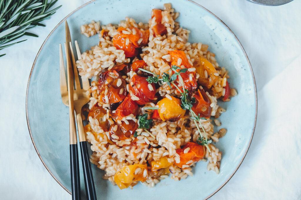 Risotto mit Tomaten auf blauem Teller mit Besteck links